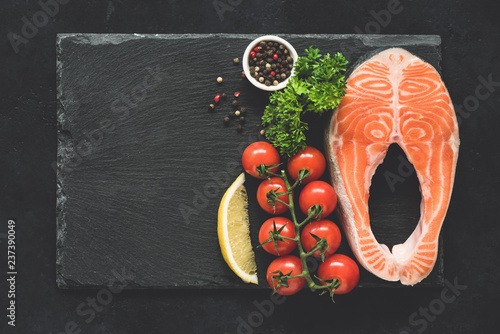 Salmon steak and vegetables on black slate background. Top view with copy space for text, menu, recipe. Healthy food background
