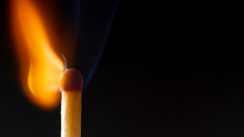 Burning Wooden Match With A Red Match Head On A Black Background.