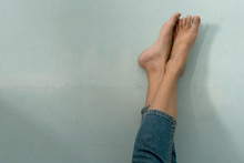 Female Legs Crossed On Blue Cement Floor.
