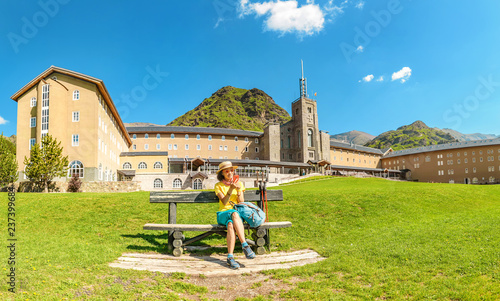 Fotografering Traveler tourist woman in Vall de Nuria Sanctuary hotel and church building in the catalan pyrenees mountains, Spain