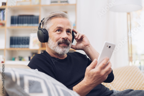 Photo  Middle-aged man listening to music online at home