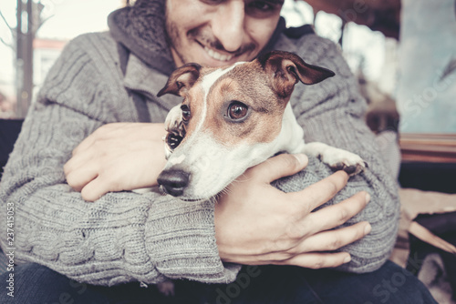 Fotografía  Man cuddling with his terrier dog in winter