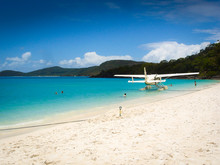 A White Beach, Turquoise Water A Water Airplane And The Blue Sky
