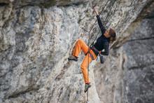 Woman Climbs Grey-color Rock In Orange Pants