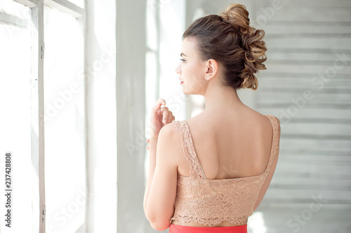 An attractive young girl stands with her back in a red skirt and upper bodice in a large window in a bright room Wallpaper Mural