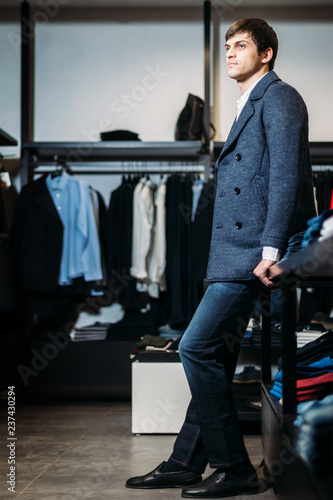 Fotografía  sale, shopping, fashion, style and people concept - elegant young man in a coat stand and waits for girls with dressing in clothing store