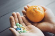 Humans hands with pills and mandarin fruit. Male hand holding pills and fruits. Vegan choice. Health food.
