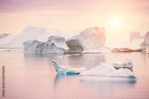 Icebergs on the shore of Atlantic ocean at sunset, Greenland
