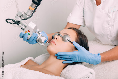 Valokuvatapetti woman getting laser facial treatment, aesthetic surgery,
