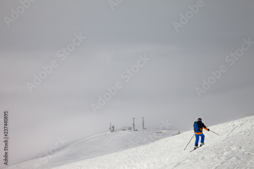 Skier before downhill on slope for freeriding and overcast misty sky