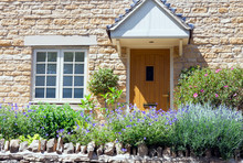 Light Brown Doors In A Limestone Golden Colored English Cottage With Flowers And Shrubs In A Front Garden, Summer Day .