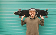 Smiling Teenager In A Cap And A Hoodie Stands On The Background Of A Green Wall, Holds A Longboard On His Shoulder, Looks Into The Camera And Rejoices. Portrait Of Lucky Skater. Copyspace