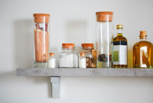 Arranged Jars With Various Spices And Olive Oil On Kitchen Shelf
