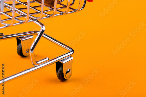 Fotomural  shopping trolley on orange background, shopaholic concept