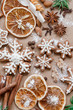 Christmas decoration with spices and cookies in the shape of snowflakes, cinnamon sticks and star anise on dark brown paper background. Top view.