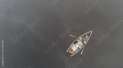 Aerial view about a very simple fishing boat on a cold autumn foggy morning near a beautiful fishing lake in Sic Canvas Print