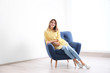 canvas print picture - Young woman sitting in armchair at home. Space for text