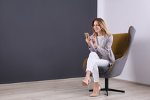 Young Woman With Smartphone Sitting In Armchair At Home. Space For Text