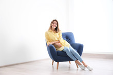 Young Woman Sitting In Armchair At Home. Space For Text