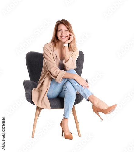 Photo Young woman sitting in armchair on white background