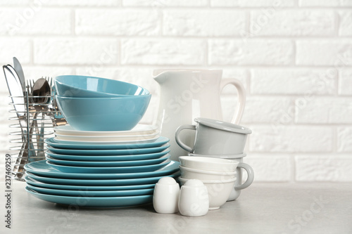 Set of clean dishes on table near brick wall. Space for text