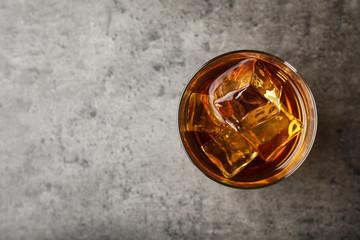 Zlatni viski u čaši s kockicama leda na stolu, pogled odozgo. Prostor za tekst