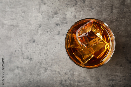 Poster Alcohol Golden whiskey in glass with ice cubes on table, top view. Space for text