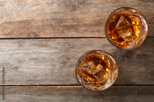 Photo Golden whiskey in glasses with ice cubes on wooden table, top view