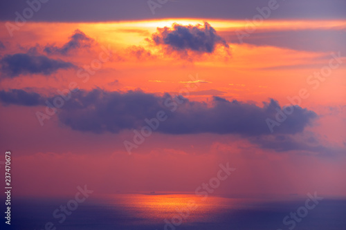 Poster Crimson Sunset cloudy sky over ocean water. Amazing landscape in bright scarlet, blue tints. Bright sky with dense clouds over water surface. Sun lights reflection. Beauty of wild untouched nature.