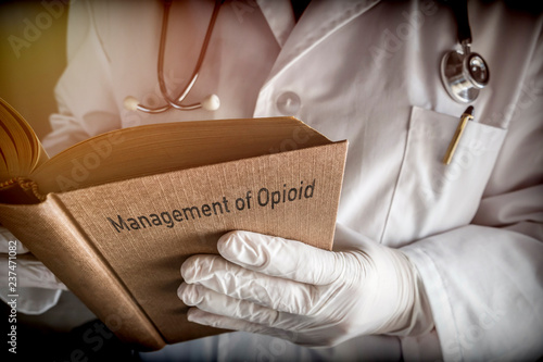 Photo  Doctor holds book on Management of Opioid, conceptual image