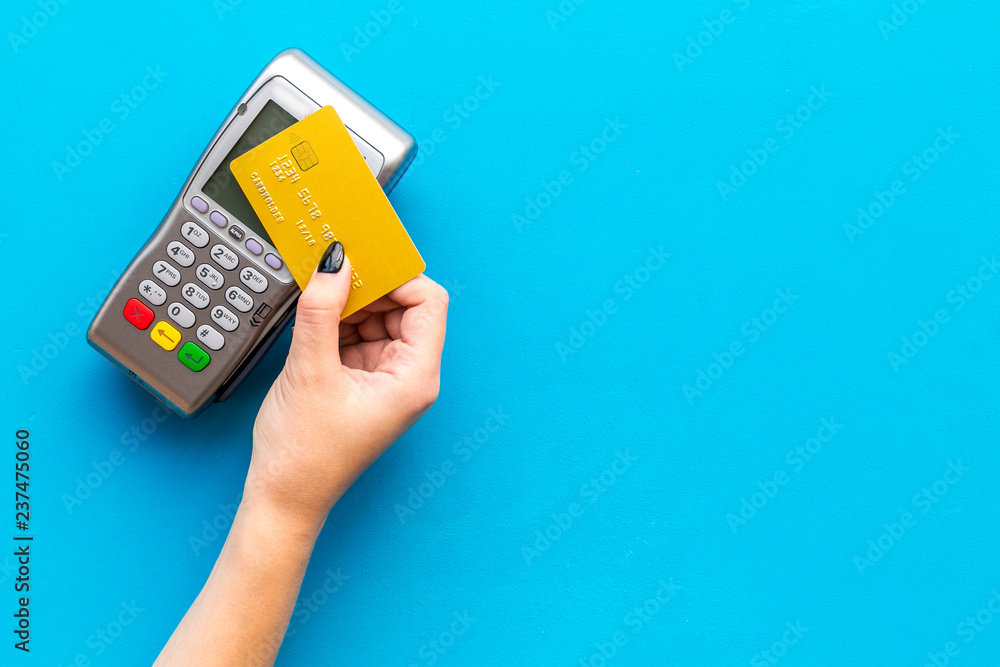 Fototapeta Pay by payment terminal. Paypass  technology. Woman's hand hold credit card, bring card to terminal  on blue background top view copy space