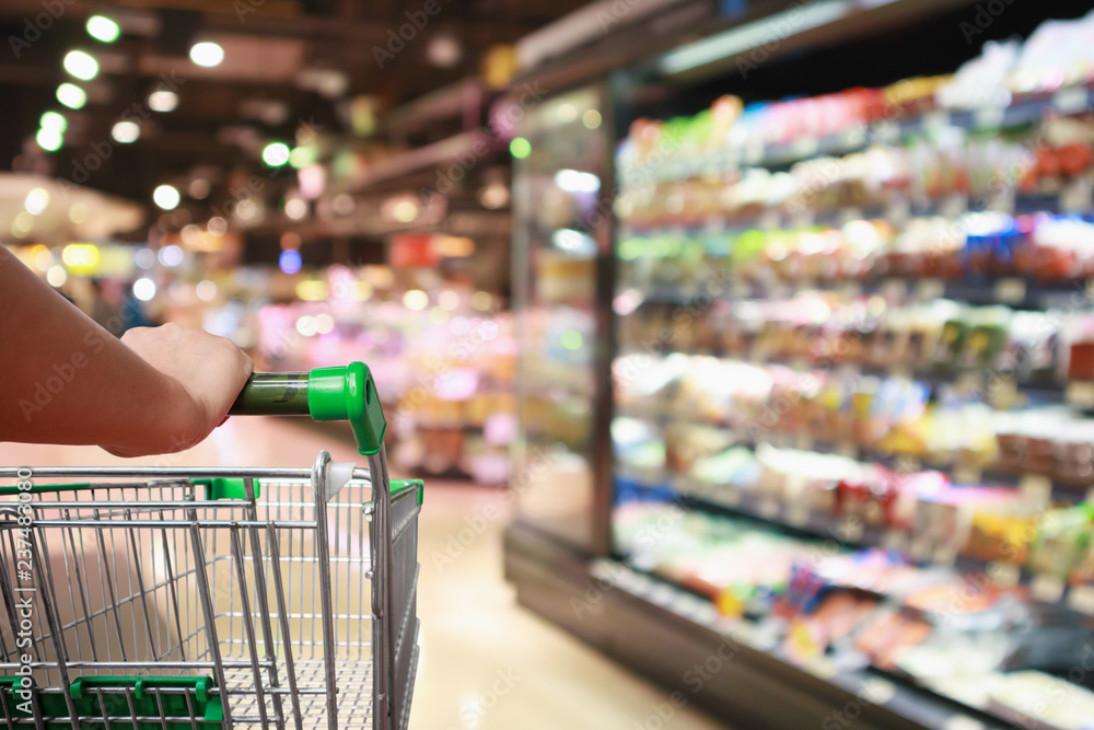 Fototapeta woman hand hold supermarket shopping cart with Abstract grocery store blurred defocused background with bokeh light