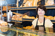 Woman baker with tasty baguettes and other bread products