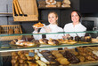 Glad woman and young girl suggesting pastry