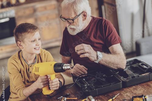 Photo  Joyful boy spending weekends with his granddad