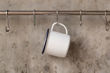White Tin Cup Hanging On Stainless Rail On Cement Wall Background.