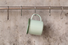Green Tin Cup Hanging On Stain...