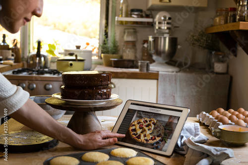 Woman reading baking recipe on a tablet