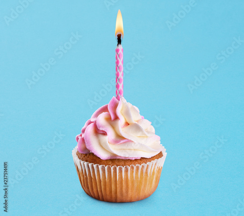 Photo  Cupcake with birthday candle on a blue background.