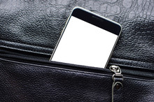 Smart Phone With White Screen For A Copy Space Looks Out From The Unzipped Leather Pocket. Zipper And Cell Phone Close-up.