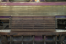 Selective Focus On The Old Wooden Vintage Chair At The Train Station With Blurred Bogey In Background. Vacancy Wooden Bench At The Platform Of Station