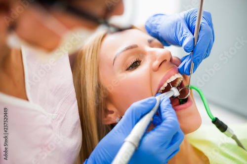 Young woman at dentist. Dentist is repairing her teeth.