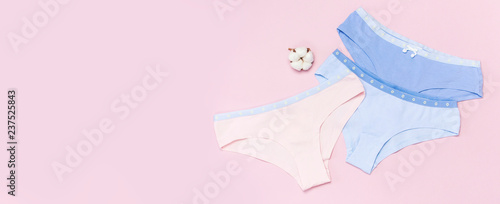 Obraz Female pastel cotton set panties and cotton flower on pink background top view flat lay with copy space for text. Fashion blog, Colorful women's natural underwear, advertising, shopping concept. - fototapety do salonu