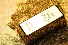 Gold Bullion On A Gold Glittering Powdered Surface.