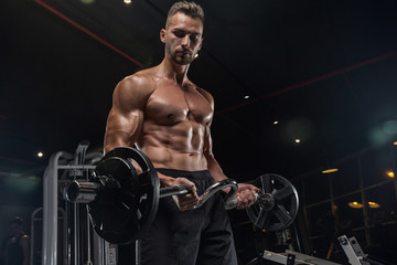 Fototapeta na wymiar Handsome man with big muscles, posing at the camera in the gym
