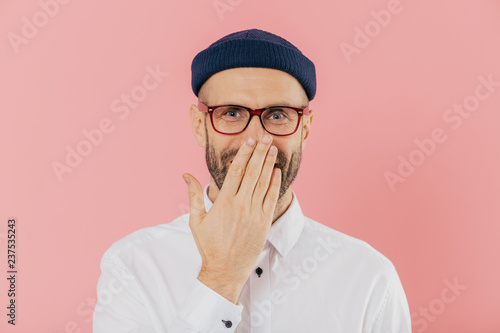 Fotografie, Obraz  Positive unshaven man covers mouth with palm, giggles positively, wears spectacles, hears funny joke, models against pink background