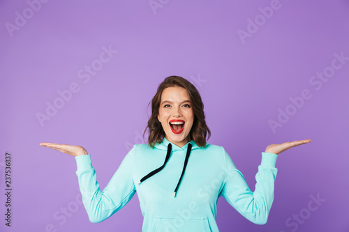 Beautiful young woman posing isolated over purple background wall.