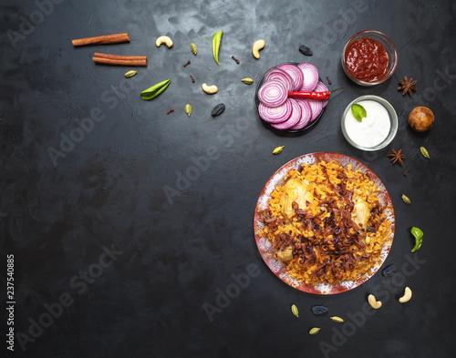 Chicken Kabsa - Homemade Arabian Biryani overhead view on black table.