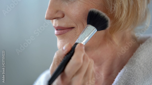 Valokuva  Mature woman applying face powder by make-up brush, preparing for date, beauty
