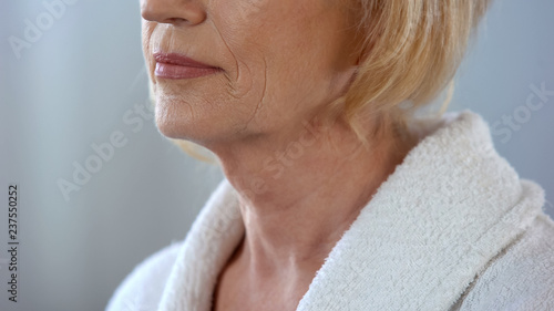 Valokuva  Elderly woman standing in bath robe and looking in mirror, body care, close up